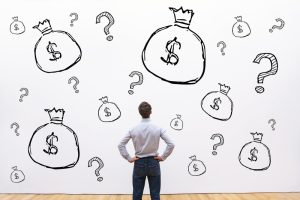 Man looking at a wall with money bags and question marks, deciding on the cheapest personal loan in Singapore
